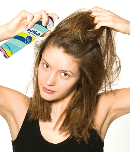 Applying Batiste dry shampoo